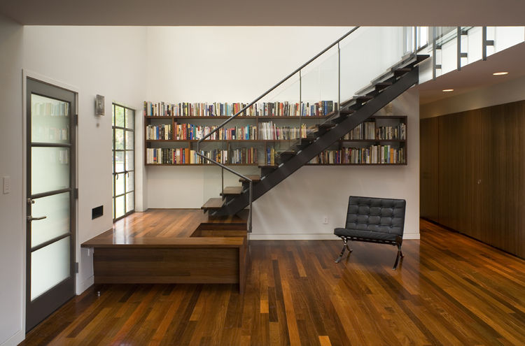 "Particularly fond of careful detail, Alter designed the treads of the entryway staircase to merge seamlessly into the adjacent bookshelves. ""I enjoy doing things that make you wonder about the context and look a little further,"" he says."