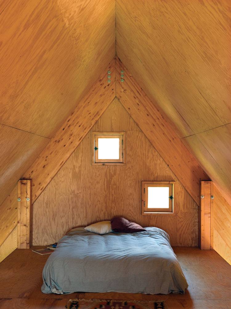 In the third-floor bedroom, peekaboo windows offer a glimpse of the surrounding fields.