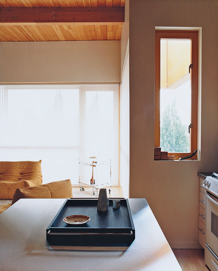 A view across the kitchen counter to the living room reveals different shades of changing light.
