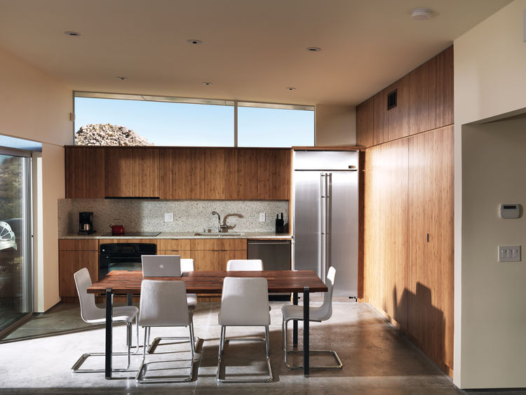 Onelarge room houses the kitchen, dining, and living area; the backsplash and countertops are made by Vetrazzo.