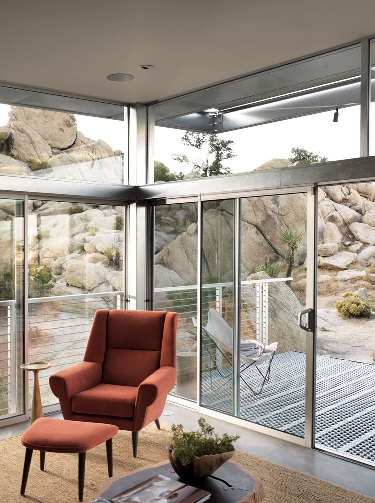 "The main living area extends to the deck through sliding glass doors. The orange David Chair and ottoman were designed by Palm Springs-based interior designer <a href=""http://www.christopherkennedy.com"">Christopher Kennedy</a> and are from his eponymous l"