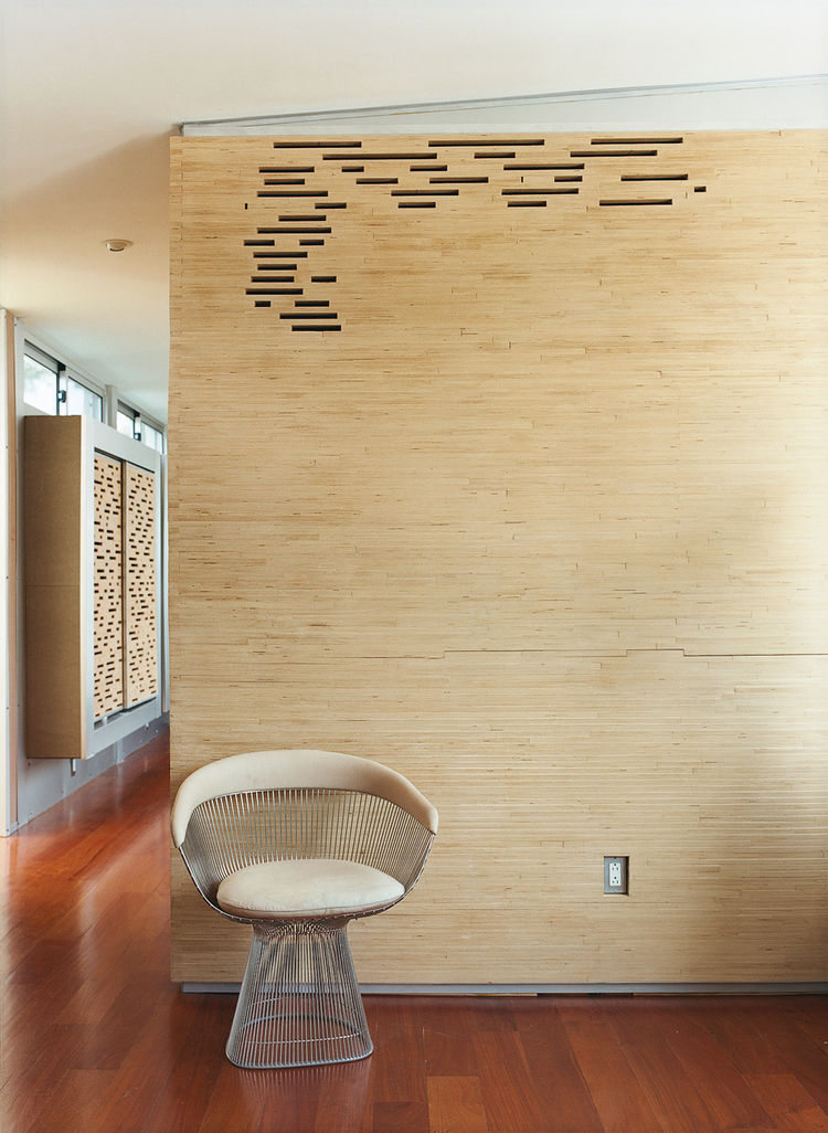 Stacked Baltic birch plywood strips encase the master bathroom, with gaps providing ventilation.