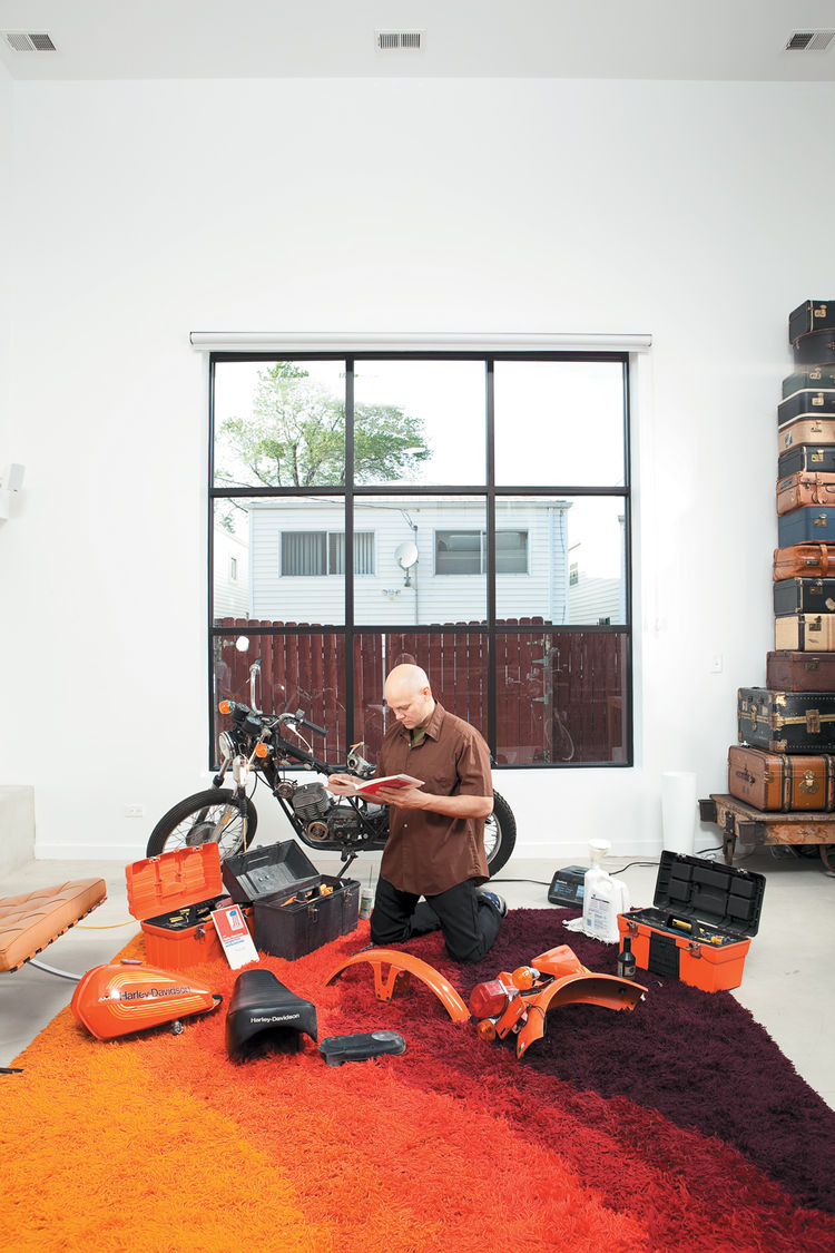 In the light-flooded living room, Hernandez does a little work on a 1976 Italian-made Harley-Davidson SXT125.