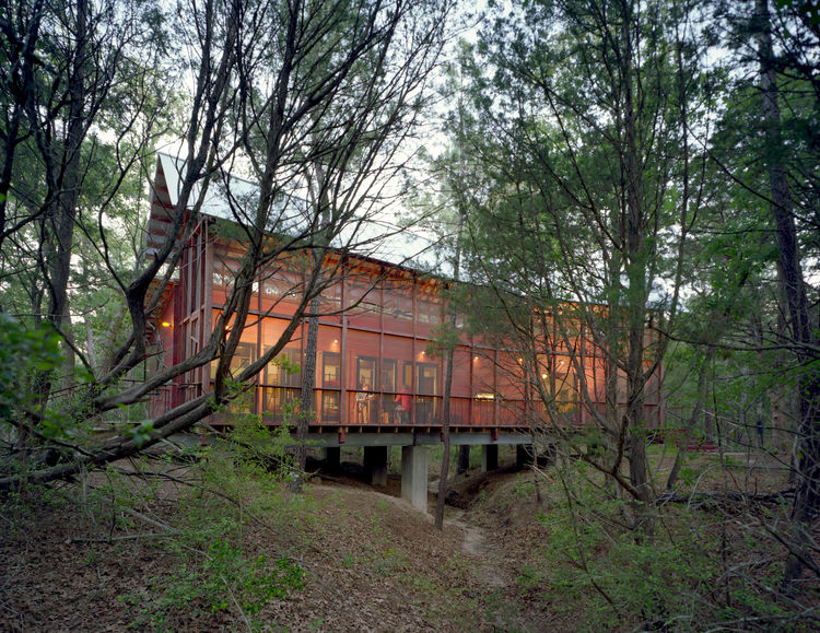 A screen porch runs the entire length of building, built over a dry creek bed on embedded concrete piers. The architect says he worked with the varying topography and native pines, turning the building 30 degrees at one point to accommodate the natural co