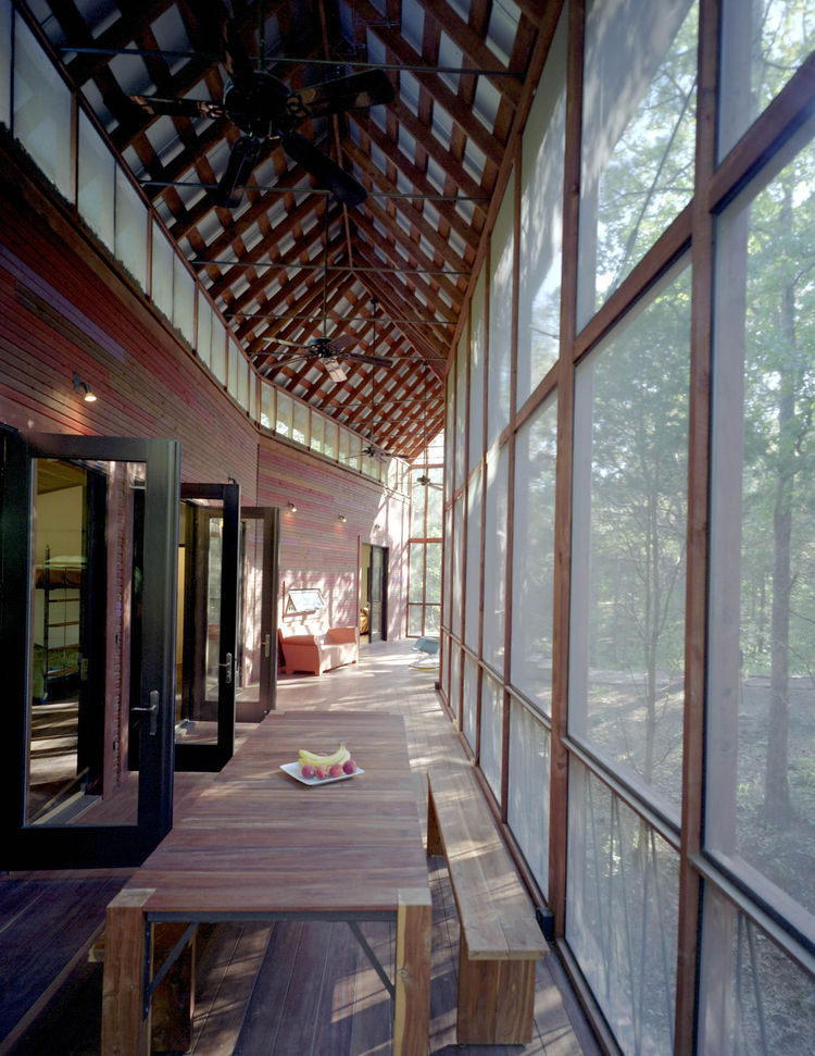 Several sets of aluminum-and-glass French doors open from the bunkroom onto the screen porch. Panton and his team made the dining table and benches on-site; the tongue-and-groove benches and table legs are locally milled cedar, and the top is Brazilian Ti