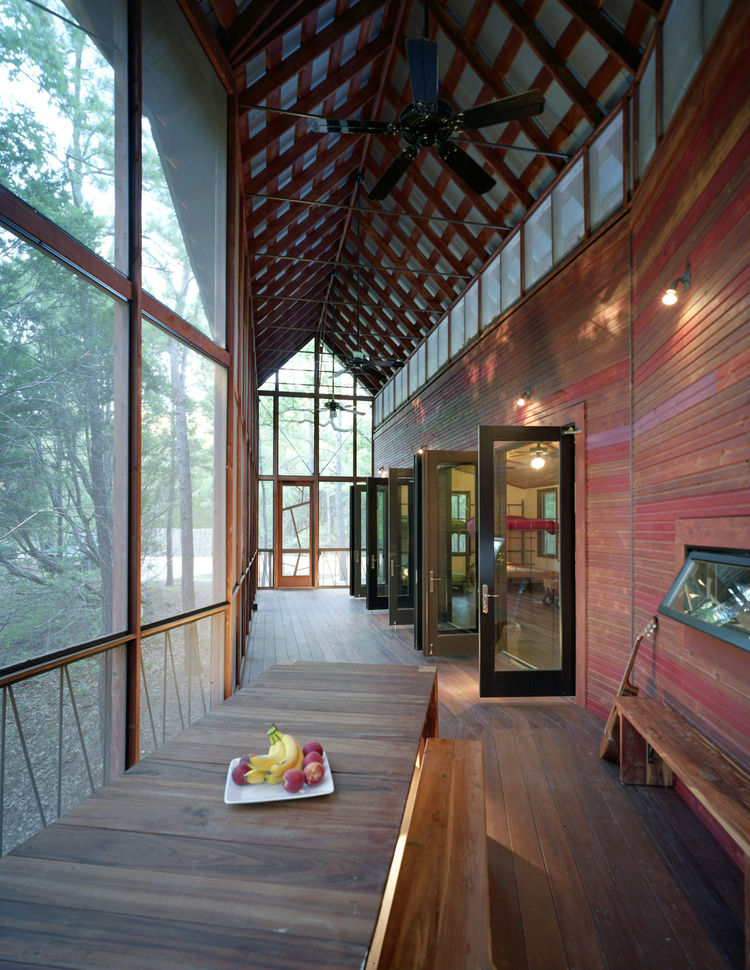 A view back toward the entrance. The purlin ceiling beneath the porch's gabled Galvalum roof is made up of two-by-four cedar strips. A frieze of screened openings runs the length of the building, allowing a cross-breeze and extra light in, while ceiling f