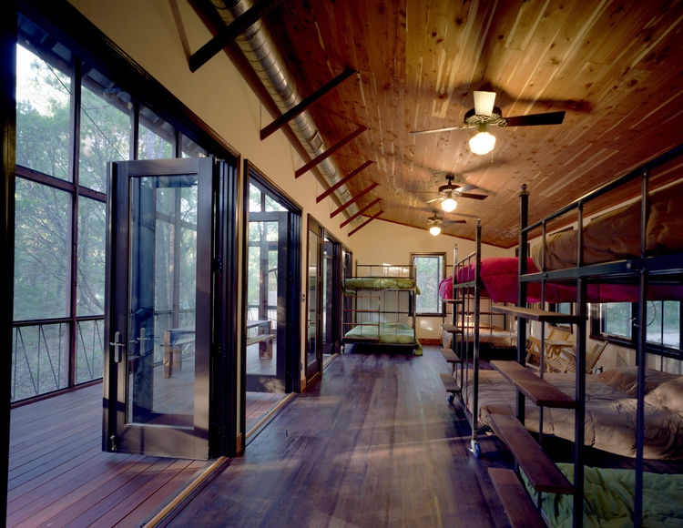 Panton placed several custom-made queen-size steel-and-wood bunk beds inside the bunkroom. All the beds are on wheels and fit through the double-side door openings, so they can be easily rolled into the porch for sleeping. Complementing the locally milled