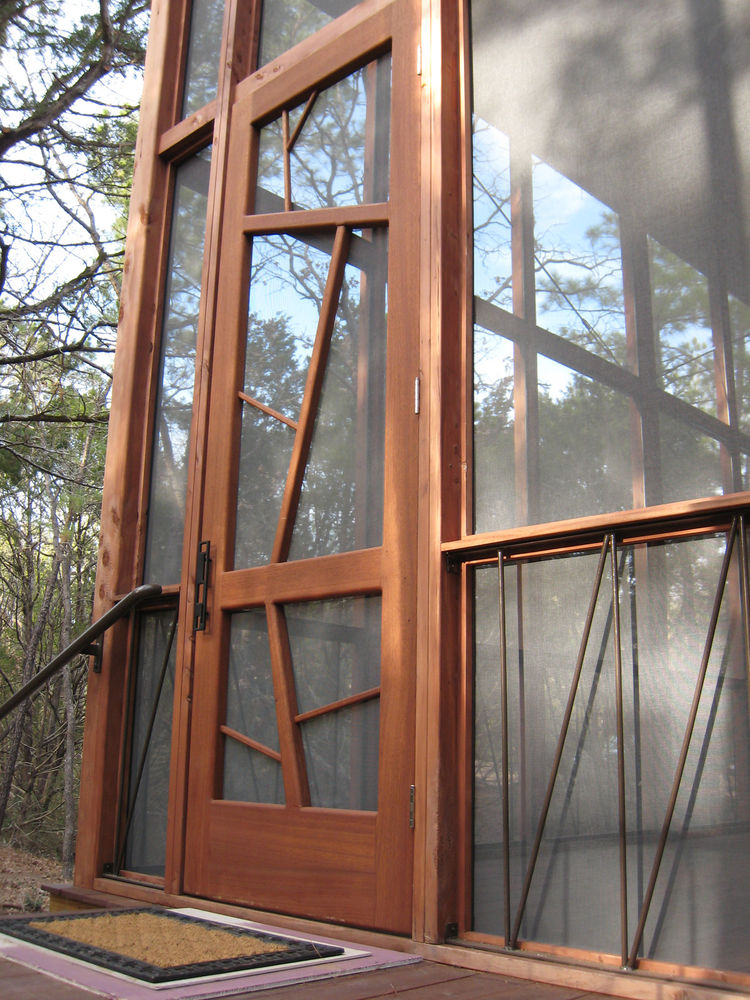 """The nine-by-three-foot mahogany entrance door is meant to evoke the surrounding trees. The iron handrails lining the base of the porch are a subtle architectural detail, as well as a support system to prevent the cabin from ever twisting or shifting """"like"""