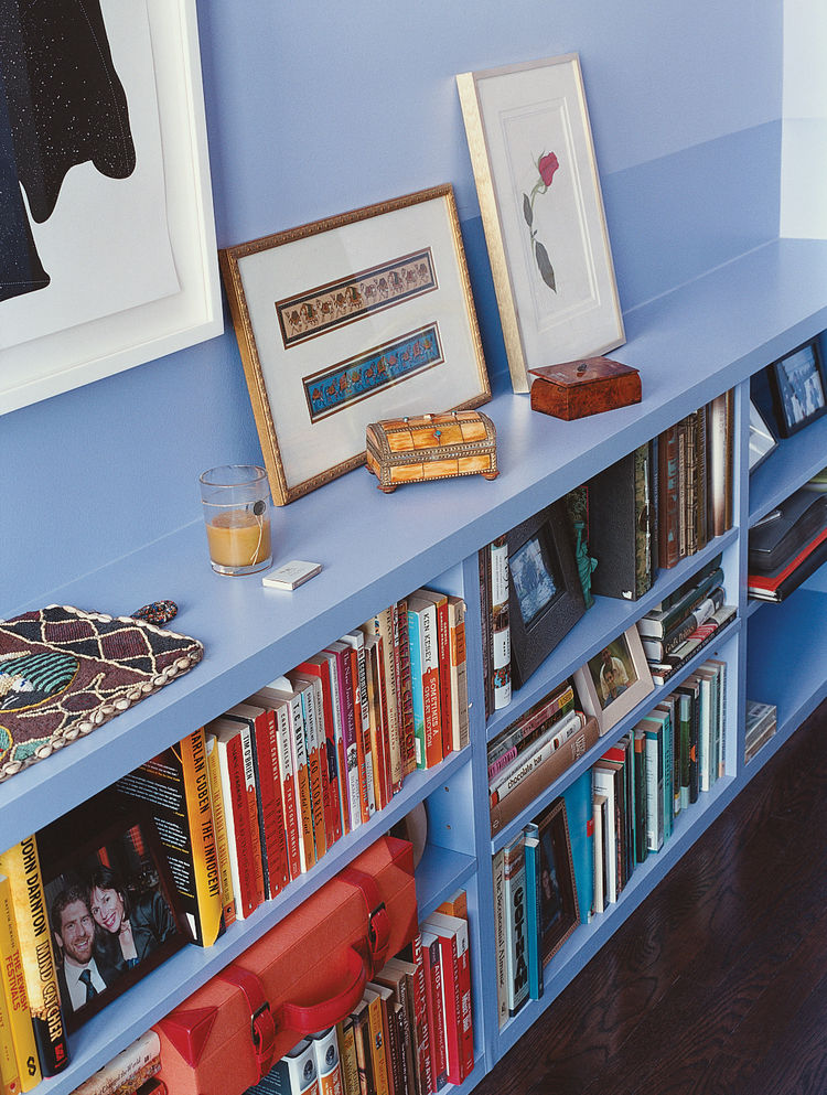 The bedroom is painted white with one blue wall and built-in shelving. Wood floors, largely rugless, are luminous and wheelchair friendly.