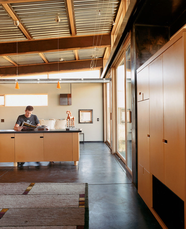 Architect Eric Logan sits in the guest house on his property. The interiors are made up of oiled masonite wall paneling, raw MDF cabinetry, and an oiled concrete floor.