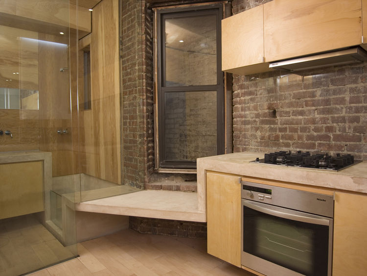 "The kitchen has a <a href=""http://www.mieleusa.com"">Miele</a> cooktop, oven and hood, as well as a small seat before a double-hung window, one of very few natural light sources in the apartment. The concrete ribbon continues into the adjacent bathroom, be"