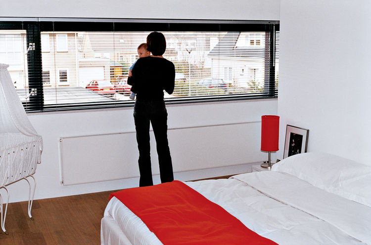 Dedy gazes out at the neighborhood from the couple's bedroom.