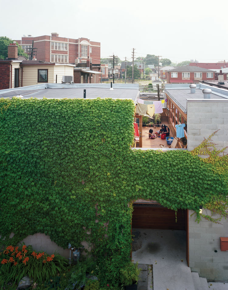 A wide cut across the top of the structure made room for a second-floor courtyard where the family can catch some sun but maintain their privacy. On the ground level, the front door is tucked into an ivy-covered alcove lined with ipe, a material used thro