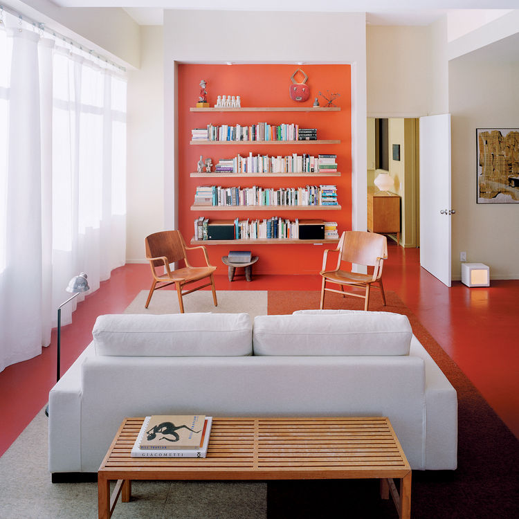 Architect Grant explains that the recessed orange wall with built-in storage shelving is a counterpoint to the view of Boston in the opposite direction.