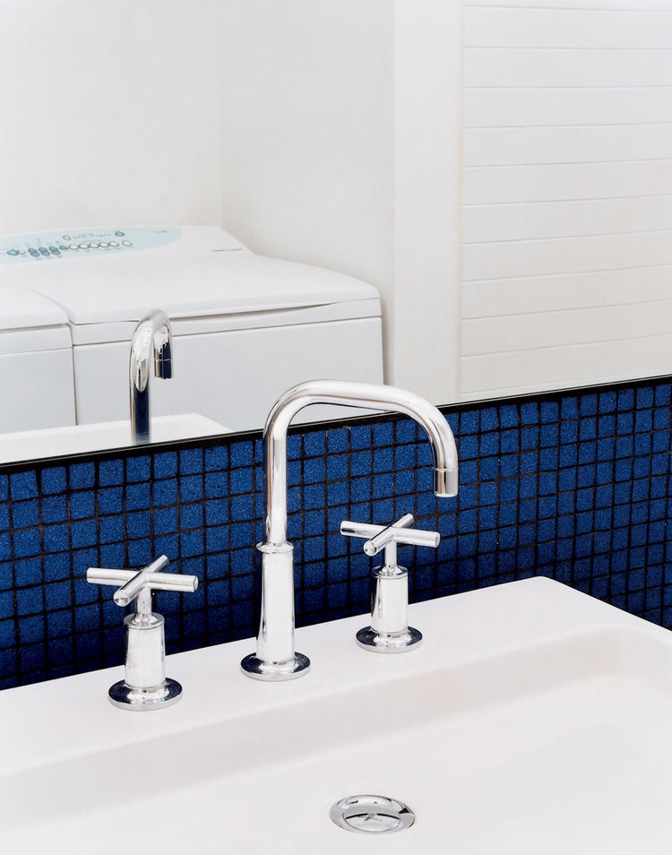 The bathroom does double duty as the laundry room. Sink, faucet, and all other bathroom fixtures throughout the house are by Kohler. The Eco-Smart washer and SmartLoad dryer are by Fisher & Paykel.