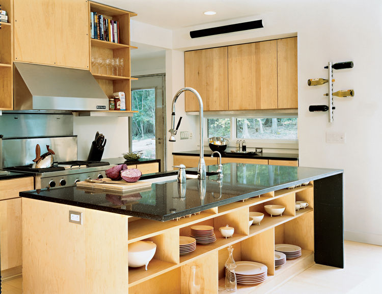 Wieler and Tung wanted a space conducive to entertaining, and this open kitchen delivers. It features a stainless steel refrigerator, Pro-Style gas range, hood, backsplash, and two-rack tub dishwasher, all from Jenn-Air. The ebony countertop, which allows