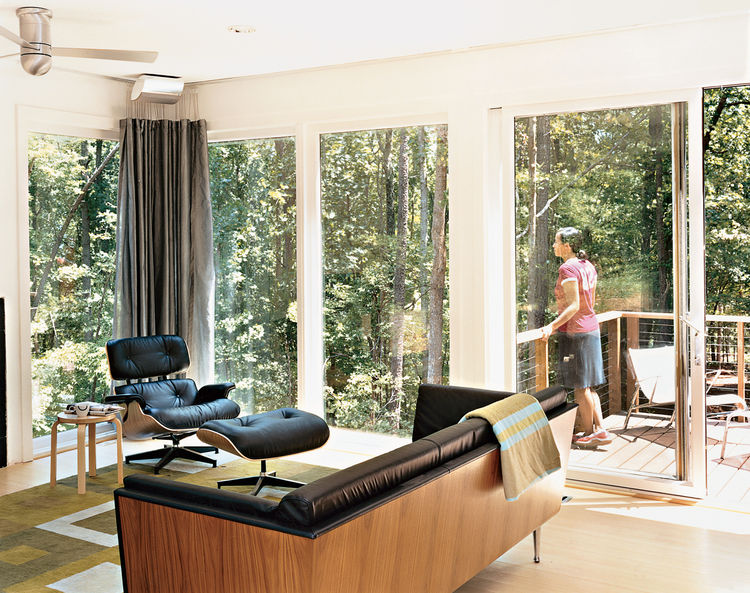 Tung takes in the wooded view from the house's back deck. Inside, the Goetz sofa, Eames lounge chair and ottoman, and Aalto stool are all from Herman Miller.The rug and throw are by Emma Gardner.