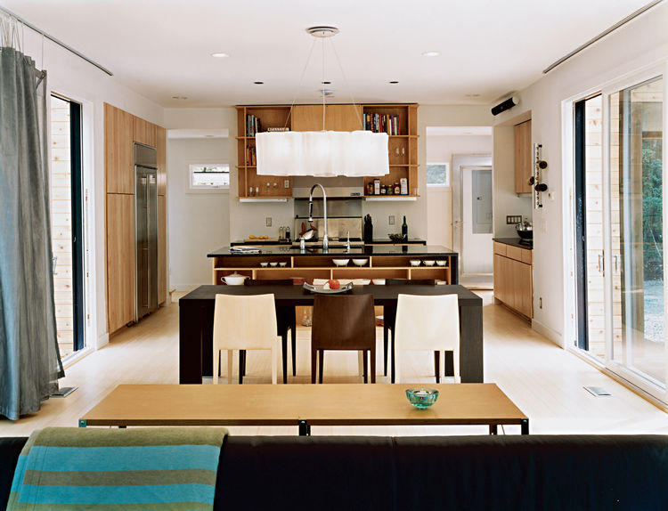 """Light-filled living and dining areas and an open kitchen are all contained within the ground-floor module. The space can be closed off by slightly iridescent curtains in """"Decipher"""" by Maharam, hung on a curtain track with 8"""" drop chains. The centerpiece o"""