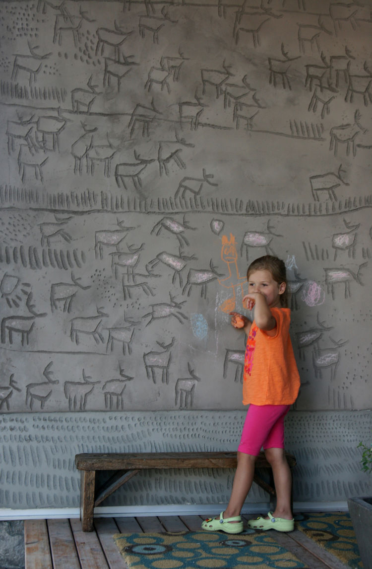 "The couple's daughter, Kalyna, puts her own spin on her father's engravings, which he calls a ""concrete coloring book."" Dedicating this side of the building to the earth, he carved herds of caribou into the panels. The abstract marks at the base skirt the"