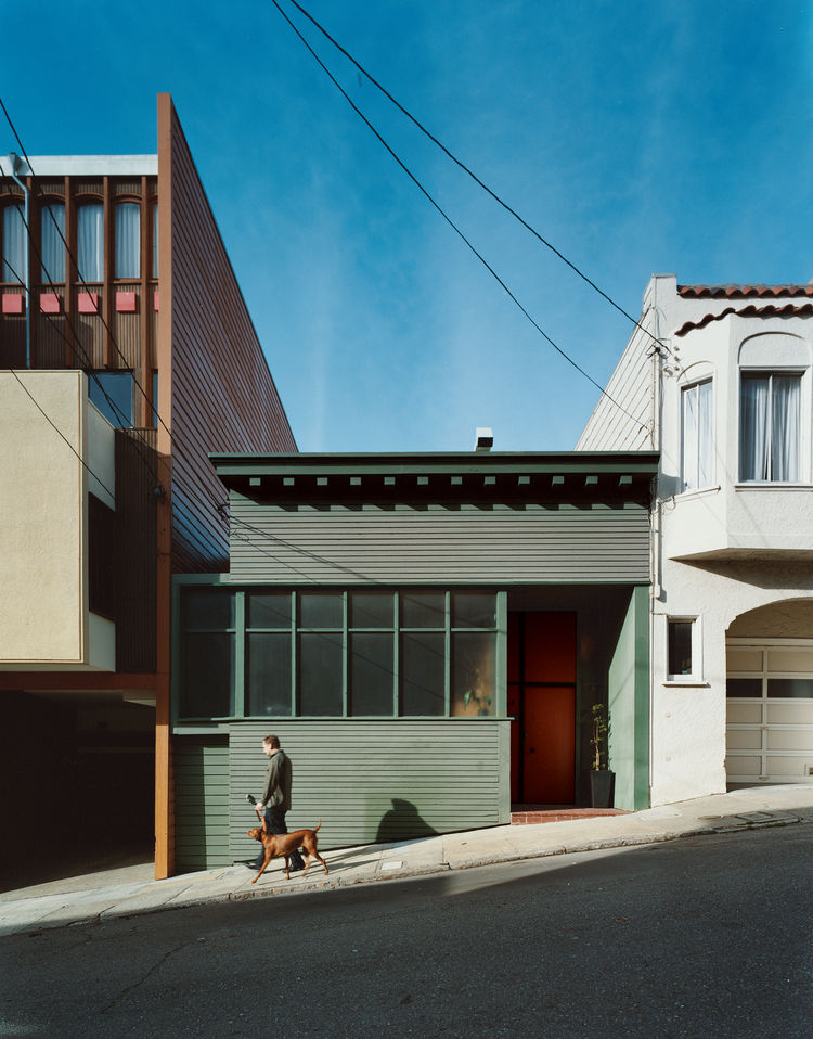 Farnham walks the couple's Vizsla, Kasia, down the sloped alley upon which the  house sits. Hill's renovation maintains some Victorian character in the decorative eaves  and scaling, but the home is largely an anomaly for San Francisco.