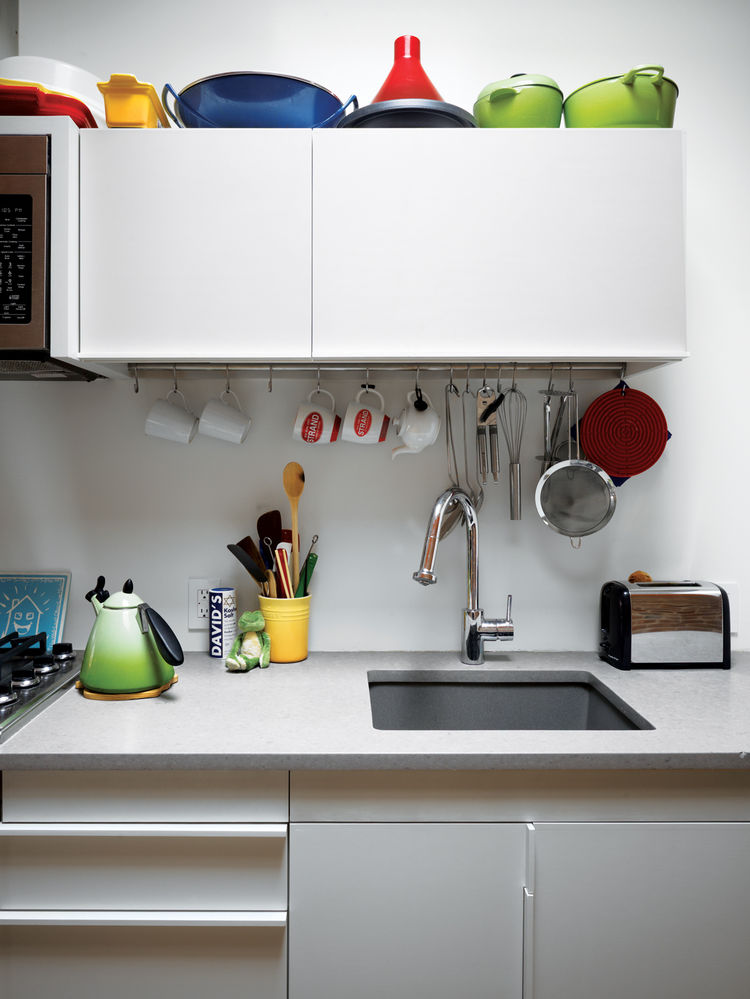 In the kitchen, colorful cookware accents white surfaces.