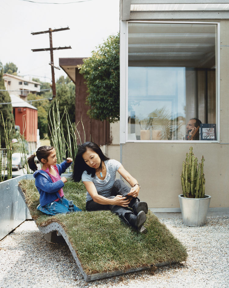 Téa gets mom ready for her close-up on the curvy nature-meets-industry chaise lounge of the architects' own design. The landscaping in front and out back is characterized by sturdy, resilient, and drought-resistant plants like bamboo and cacti, cultivated