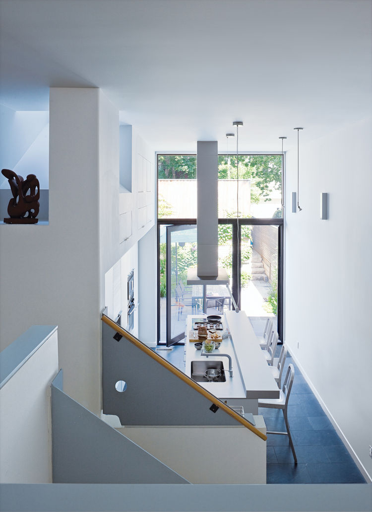 Since the room is at the windowless middle of the house, it borrows light from the kitchen, which, despite its pristine Bulthaup cabinetry and hardware, is the laid-back heart of the house. Chong took advantage of the one-and-a-half-height ceiling to esta