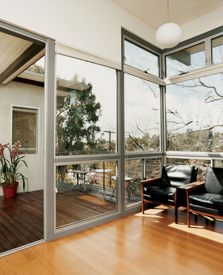 The second-floor deck looks out onto the green canopy of Garcetti and Wakeland's neighborhood and indoors to a pair of Vatne Møbler rosewood lounge chairs.