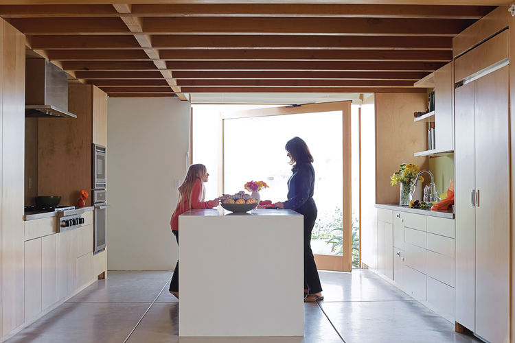 Carole and granddaughter Allison—–silhouetted against a glass door that pivots open to the front garden—–plot how they'll prepare the family's next meal at the kitchen island.