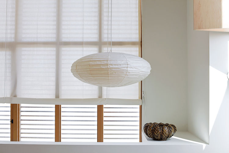 Inexpensive muslin makes a lightweight and luminous covering for windows and the pivoting glass door in the kitchen. While the roll-up shades fabricated by Van Nuys Awning Co. resemble a ship's sails, the hardware for the cords calls to mind boat cleats.