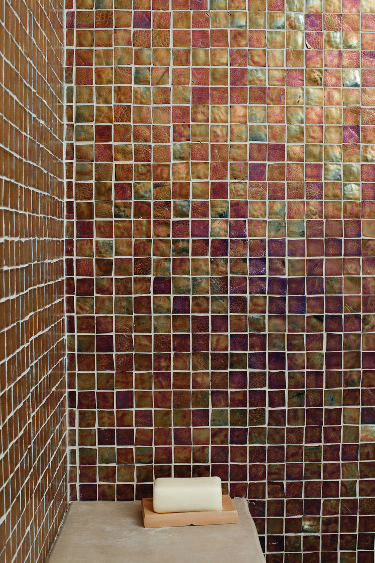 The bathrooms feature Oceanside Glasstile recycled glass tiles from Mission Tile West, in palettes inspired by the home's coastal setting. The ground-floor bathroom is tiled in brown like the earth, the guest bathroom in seafoam green, and the master bath
