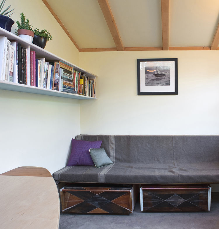 "Inside, Deeds created a wall-to-wall sofa (supported by a square steel tube) with storage drawers underneath. A single shelf provides more storage. ""The thick insulation and the passive solar features perform wonderfully,"" says Deeds. ""The building is ver"