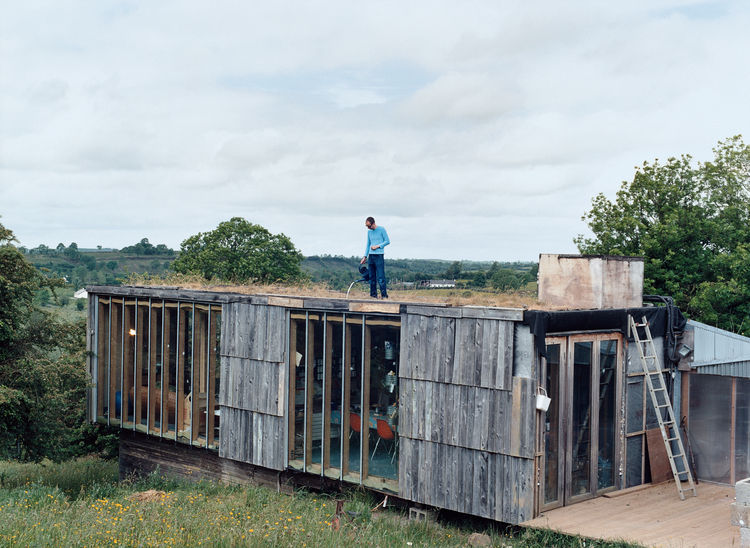 Atop a living module that contains a kitchen and eating and living areas, Dominic Stevens waters the sod roof, which, like the rest of the house, is a perennial work in progress.