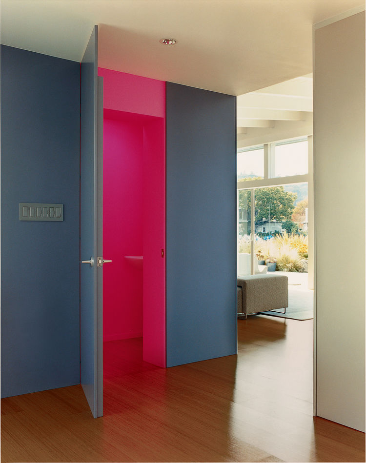 In the foyer, Deam left one surprise: The neon-pink guest bathroom is hidden behind heavy, dark-gray walls.