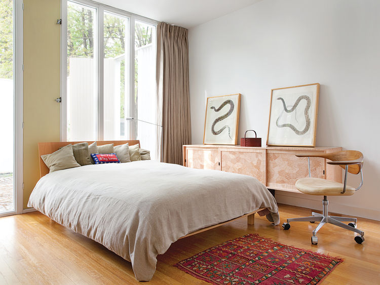 The second bedroom has an eclectic mix of textiles and textures: replicas of the original curtains, a custom wood credenza by Gerald Curry, a bright pillow made by a friend, bed linens from Finland, and a rug from Morocco.