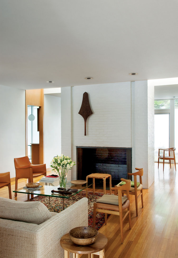 A club from the Fiji islands is mounted on the wall of the fireplace that divides the living and dining rooms. The dining room—furnished with two Cab chairs by Mario Bellini for Cassina, a pair of Cowhorn chairs by Hans J. Wegner for Johannes Hansen, the