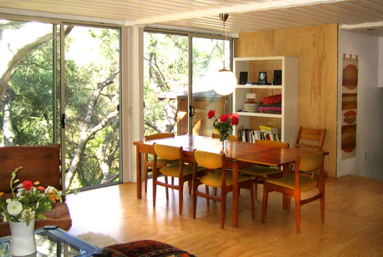 "The dining area overlooks the oak grove; the original cabin can be seen beyond the glass doors. Jantzen placed the addition about two feet higher than the cabin, reached by a small staircase at right. ""The containers are not only recycled, they're very st"