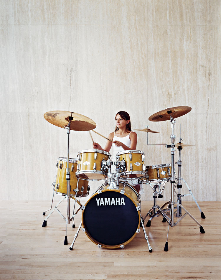 Berlin Jespersen, 8, daintily rocks the family drum kit, which Brent is also learning to play.