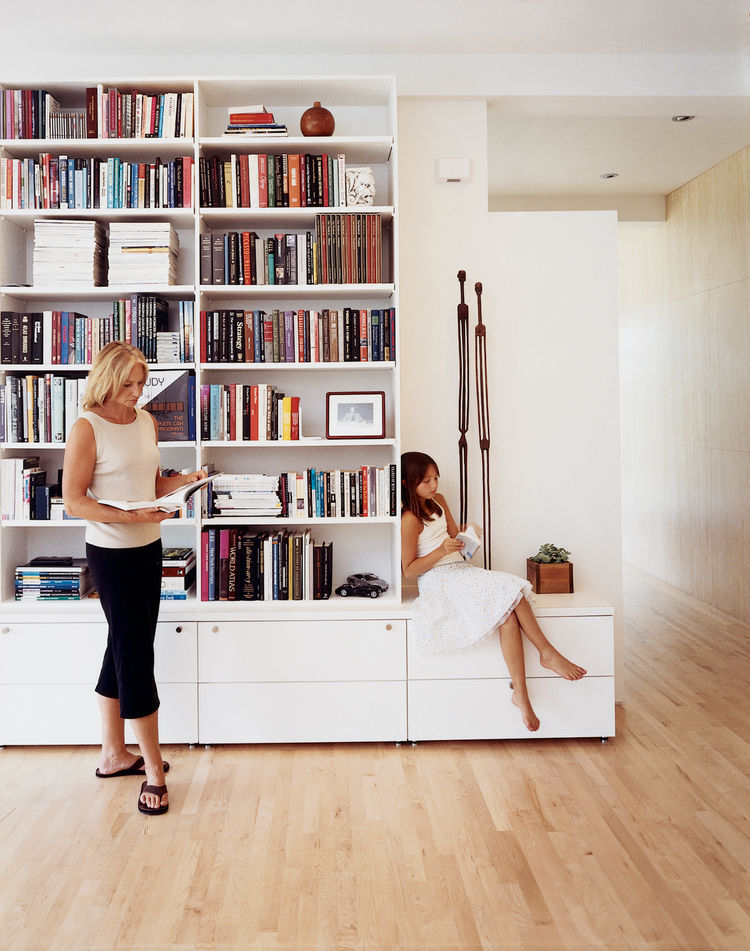 The main living room, separated by a freestanding wall, continues into an open study. The bookshelves, close to ten feet tall, are home to numerous architectural books, philosophy texts, and the literary work of Ayn Rand. Recessed speakers emanate music t