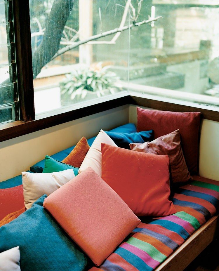 The exposed wood and raw concrete throughout the house are offset by bold colors, chosen by Shelly and the children. The house's warm hues can clearly be seen in this window seat in Ray's office.
