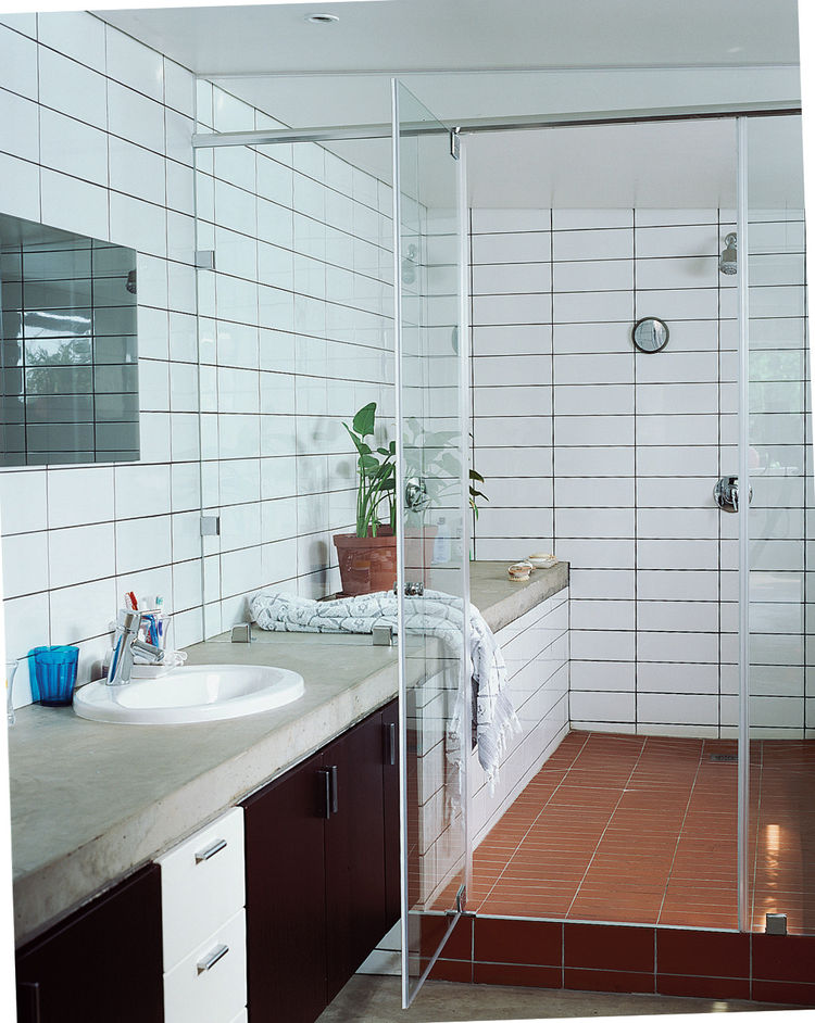 The shower-and-bath-in-one allows for the open feel of the house to translate within the bathroom. Simple concrete slabs function as countertops with inexpensive tiles laid floor to ceiling.