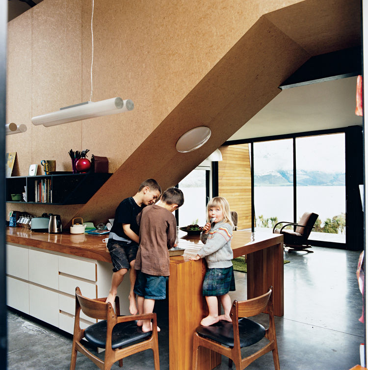 "The kids, Archie, Linus, and Olive, stand in the kitchen, beneath the strand board–clad stairwell that leads to the bedrooms. Kerr and Ritchie initially envisaged rich materials for the interior, but changed their minds in favor of what they call a ""carto"