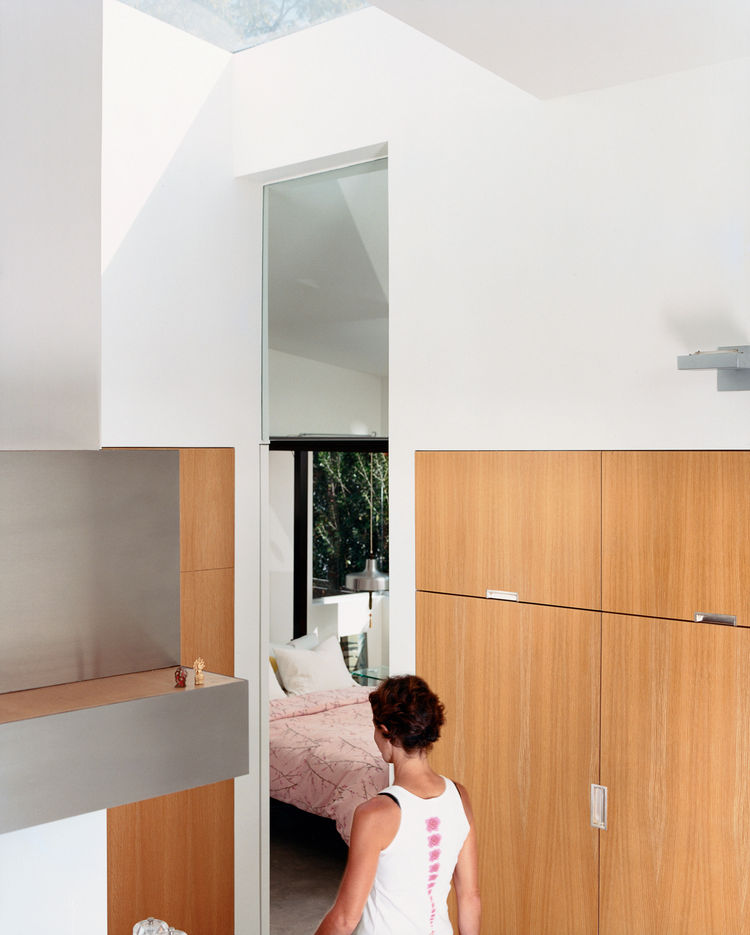 Dawn Farmer walks from the kitchen to a guest bedroom. The seven-foot-tall doorway lines up with the glass doors and cabinetry throughout the house—which is made of  13-layer multi-ply apple core with rift-oak veneer.