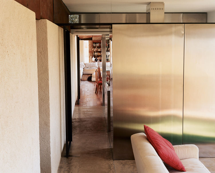 Clemente and her partners used the geometry of the podere as their guide for the house's design, creating a glazed living room that is cleaved in half by a line (a hallway at one point, a wall in another) that connects visually and spatially with one of t