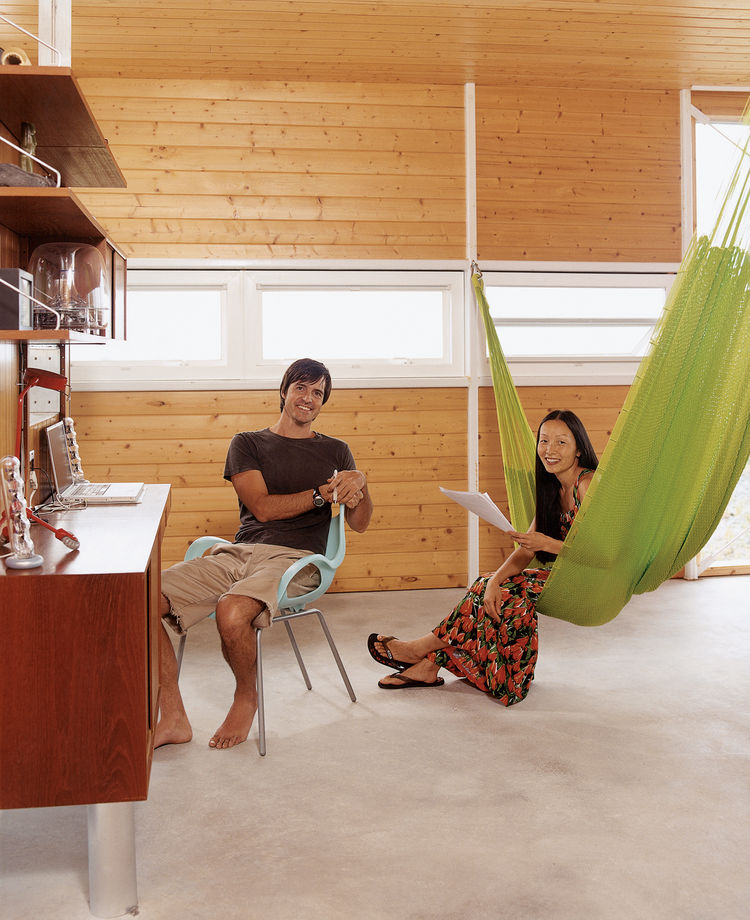 "A vintage suspended wall unit serves as a home office. Cathy demonstrates the ""third bedroom""—a three-person hammock from Oaxaca."
