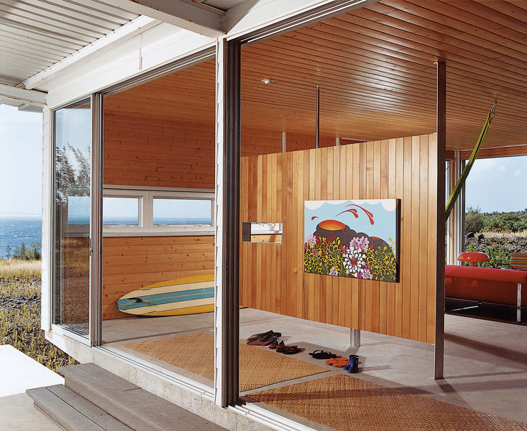 A small room divider offers a place to hang Cathy's painting Pelevision, which was inspired by her first trip to the island.