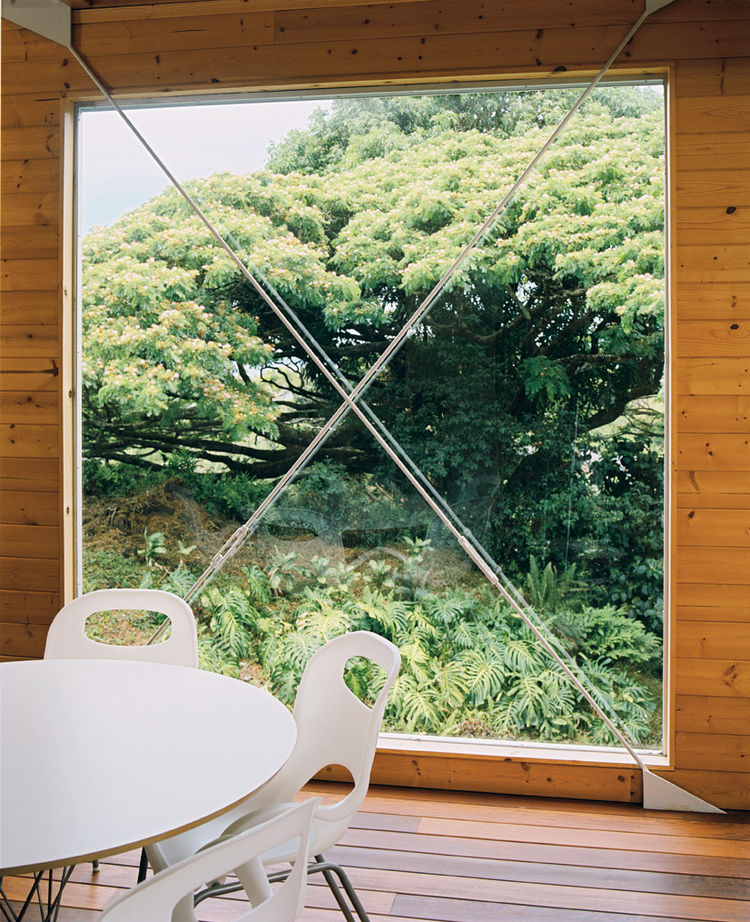 A huge window next to the dining area is punctuated by a steel X form.
