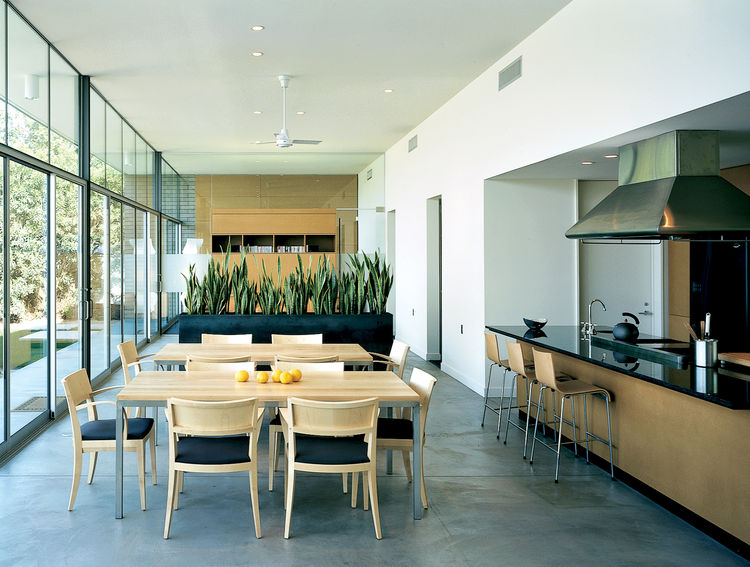 In one of three three buildings, spaces for dining, conversation and watching TV are found. The open kitchen, offices, and library are off to one side of this axis, while a north-facing window faces the courtyard.