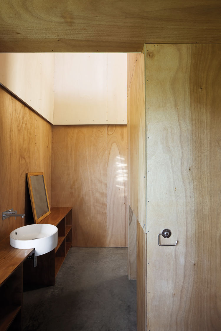 The Gaboon-plywood walls flow through into the bathroom without a door to get in the way.