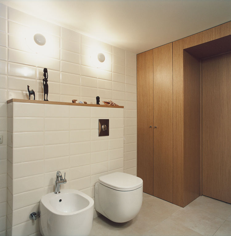 In the bathroom, which is tucked under the mezzanine, the toilet-bidet set from Pozzi Ginori boasts rounded rectangles with pleasingly deep but minimal basins. The wall sconces are from the Spanish lighting company Vibia, and fit neatly between brick-like